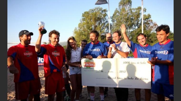 Gustavo Conti junto a Pedro Alfonso, quien alza la copa del campeón y recibe la donación de 1.000 litros de leche (Foto: La voz)